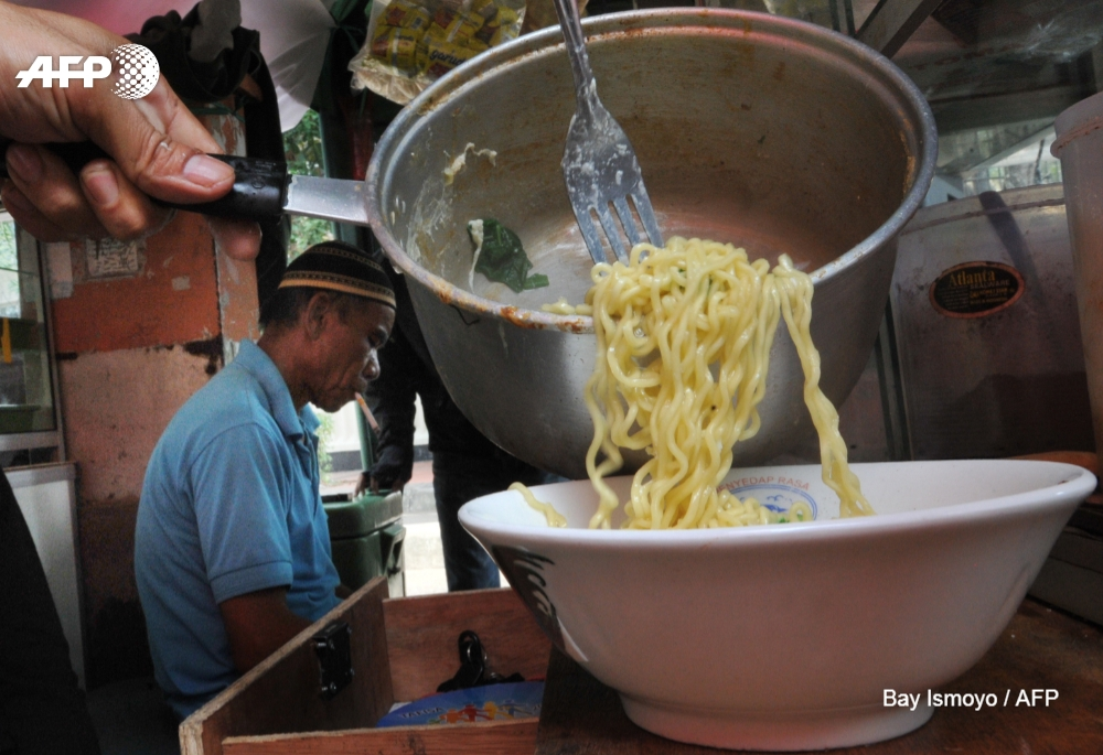 A vendor prepares instant noodles at a stall in Jakarta
